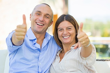 Older couple smiling giving the thumbs up