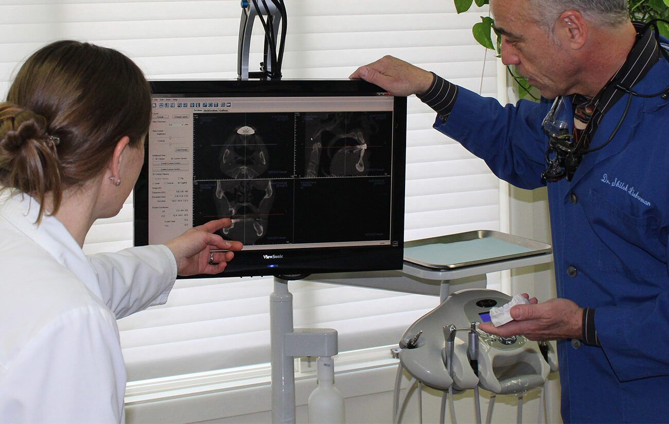 Dr. Lieberman and dental team member examine x-rays
