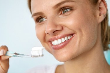 Beautiful woman brushing her teeth to care for dental implants