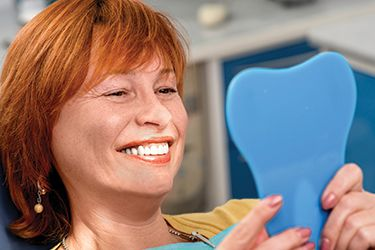 Older woman examining smile in mirror