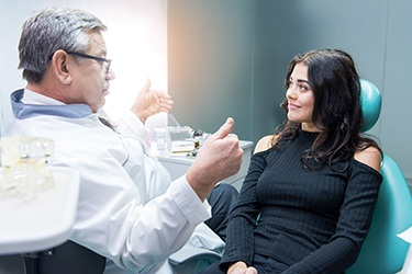 Happy female patient and dentist discussing Invisalign treatment