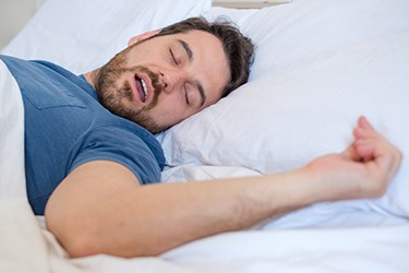 Man snoring fitfully in bed