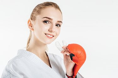 young karate woman holding mouthguard