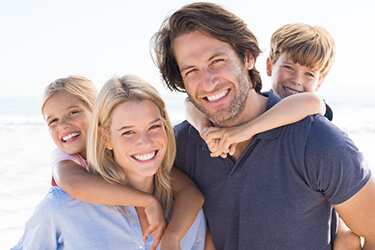 Smiling family of four on beach