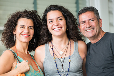 Parents and adult daughter smiling