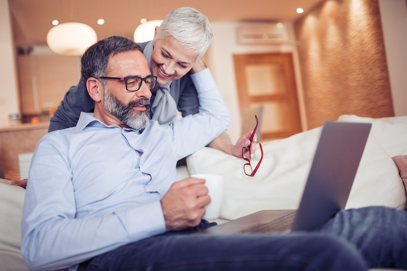 Happy mature couple using laptop in the living room.