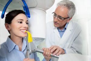 Dentist positioning female patient inside cone beam scanner