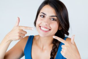 Happy woman showing off dental implants in Schenectady